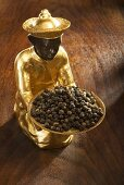 Gilded statuette with bowl of black peppercorns