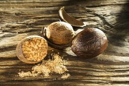 Nutmegs, shelled and grated on wooden board