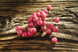 Pink pepper on wooden background