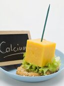Cheese on cocktail stick & slate board with the word Calcium