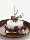 Goat's cheese, olive and rosemary on cracker