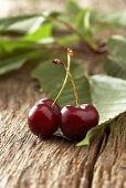Two cherries with leaves on wooden background