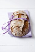 Wholemeal bread with ribbon on purple fabric napkin