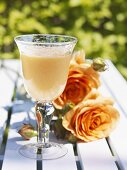 Mango lassi on garden table with roses