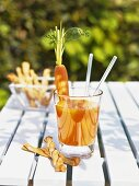 Carrot drink with grissini on summery garden table