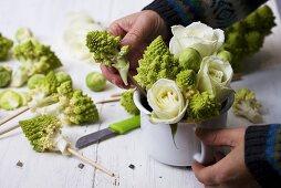 Arranging roses, romanesco & Brussels sprouts in enamel pot