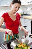 Woman frying vegetables in wok frying pan