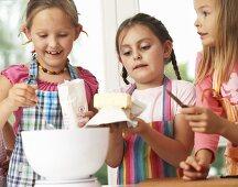 Three girls making waffle batter