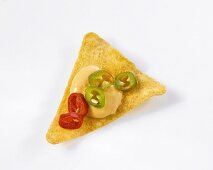 A nacho chip with cheese dip (close-up)
