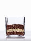 Red and white quinoa in a square glass