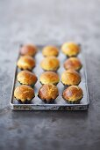 Brioches in small baking tins on a baking tray
