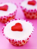 Three cupcakes decorated with marzipan hearts