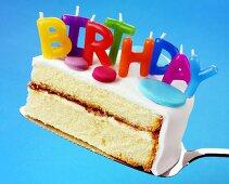 Ein Stück Geburtstagstorte mit Buchstaben-Kerzen: 'BIRTHDAY'