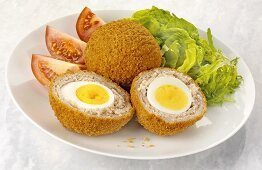 Scotch eggs (hard-boiled eggs wrapped in sausage meat) with salad