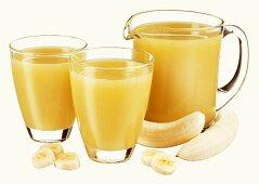 Banana juice in jug and two glasses and fresh banana