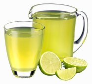 Lime juice in jug and glass and fresh limes