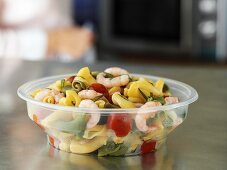 Pasta salad with prawns in plastic container to take away