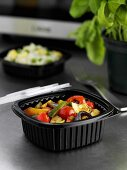 Vegetables in plastic container in front of microwave oven