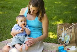 Baby eating carrot at picnic with mother
