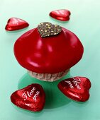 Muffin with red icing and chocolate hearts