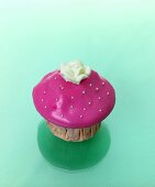 Muffin with pink icing and sugar flower