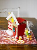 Christmas sweets and cardboard house on table mat
