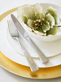 Place-setting with gold underplate, white plates, cutlery and flower