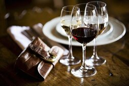 Glasses of different wine, place-setting and purse