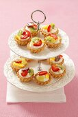 Mini fruit tartlets with vanilla cream on a cake stand