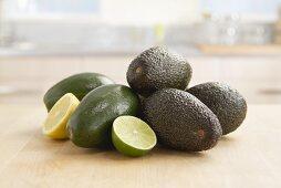 An arrangement of avocado, lime halves and lemon halves