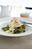 Fish fillet and prawns on potato salad with vegetables