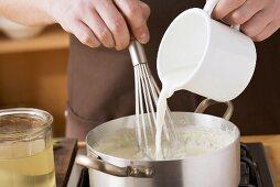 Milk being add to roux