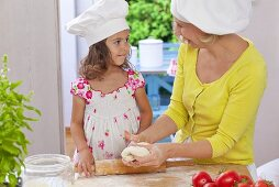 A mother and daughter kneading pizza dough