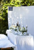 A white, elegantly laid table in a garden