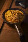 Curry powder in a wooden spoon