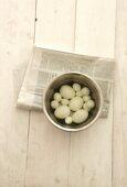 Eggs in a saucepan on a newspaper