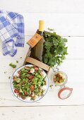 Vegetable salad, bottles of dressing and parsley in a basket