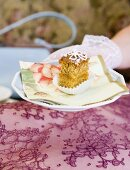 Hand holding a plate with a piece of poppy seed cake