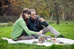 A couple having a picnic in a field in autumn