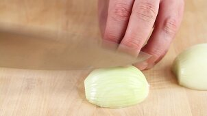 An onion being halved and diced