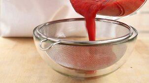 Raspberry sauce being sieved