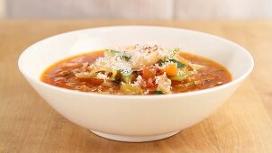 Minestrone being sprinkled with parmesan