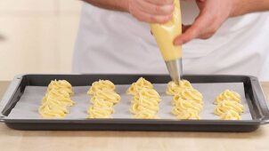 Choux pastry being piped onto a baking tray lined with greaseproof paper