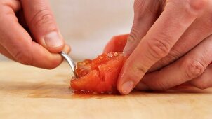A peeled tomato being quartered and deseeded