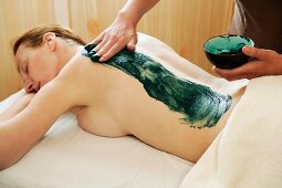 Green mud being applied to a woman's back