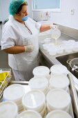 Woman putting dessert into plastic pots (canteen kitchen)