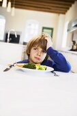 A Little Boy Looking Unhappy in Front of a Plate of Vegetables