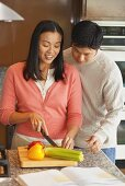 Young couple chopping vegetables in kitchen