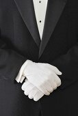 A Waiter with Crossed Gloved Hands