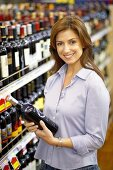 Smiling woman holding bottle of wine in a supermarket